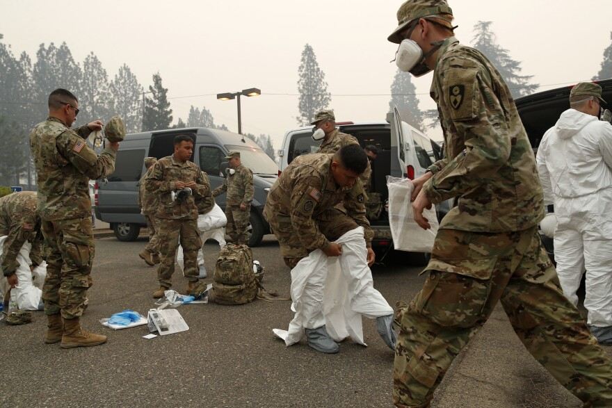 Members of the California Army National Guard put on protective suits before searching for victims of the Camp Fire in Paradise, Calif., on Wednesday.