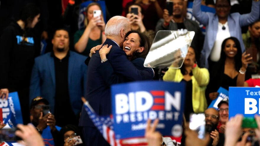 Biden hugs his former primary rival and future running mate, California Sen. Kamala Harris, after she endorsed him at a campaign rally in Detroit on March 9.