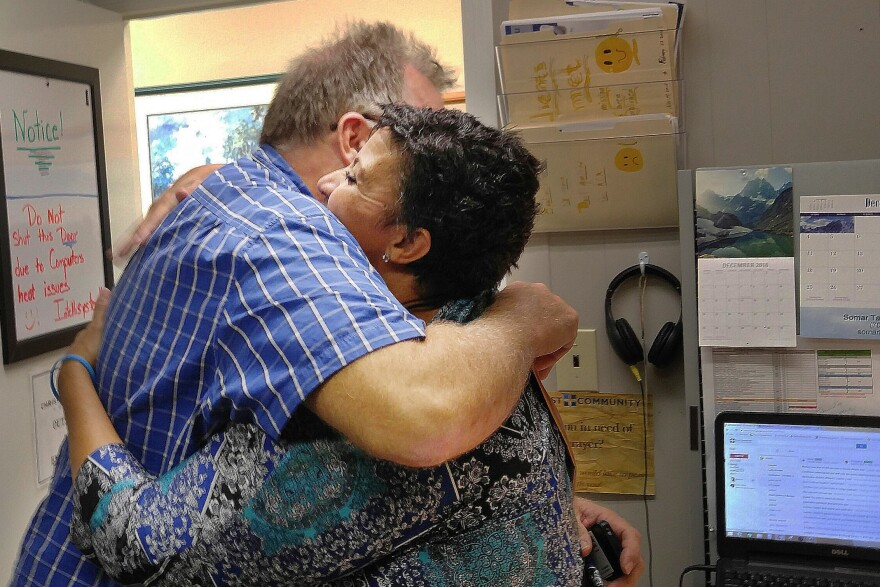 Ron Ellis of Augusta, Ga., hugs Monica Baldwin, a navigator with Christ Community Health, after she helped him sign up for insurance through the Affordable Care Act.