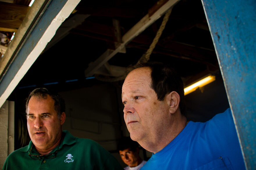 Day Boat Seafood co-owners Scott Taylor (left) and Howard Bubis watch workers unload thousands of pounds of catch from a long-line boat that was out for 10 days at their boathouse in Fort Pierce, Fla.