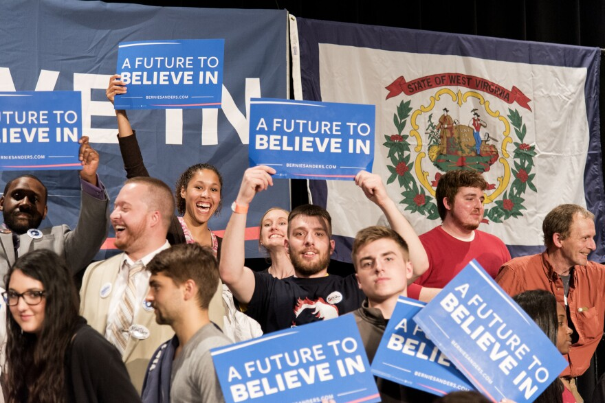 Megan Collins (top row, holding highest sign) stands behind Bernie Sanders' podium Thursday, May 5, at the Morgantown Event Center.