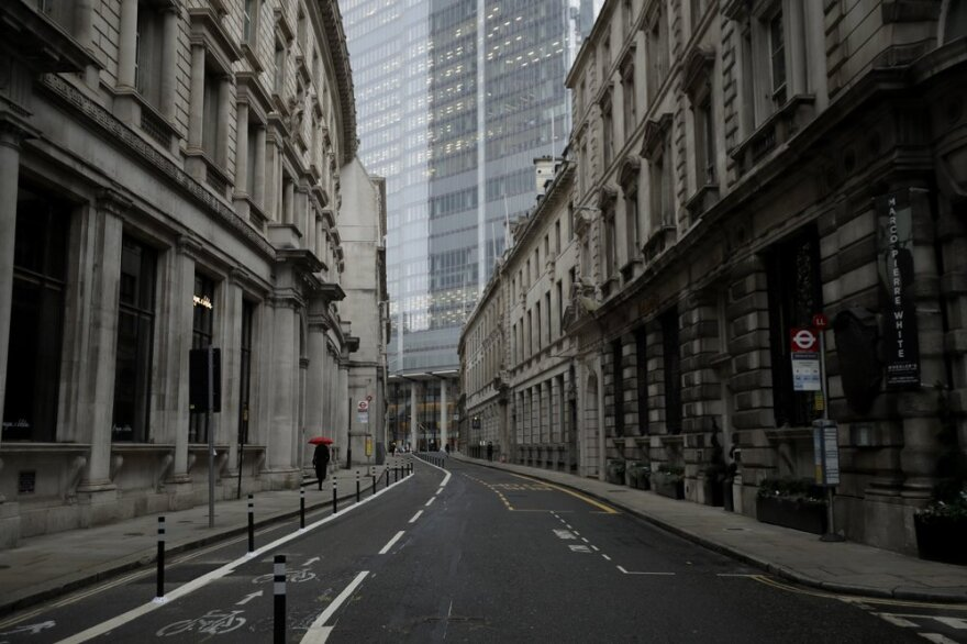 A lone person walks down the sidewalk of a deserted street in London.