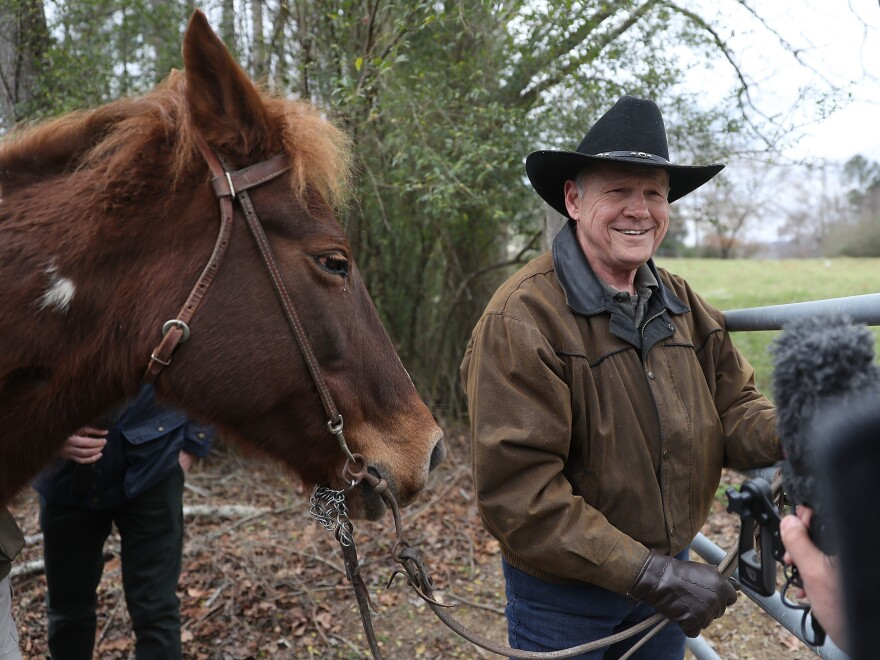 Republican Senate candidate Roy Moore rides in on a horse to vote and is pictured preparing to tie it up.