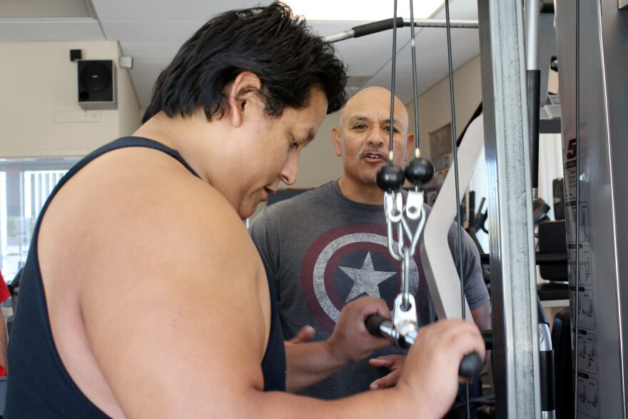 Jorje Mendez has lost more than 45 pounds through weightlifting and other lifestyle changes. Trainer Johnny Gonzales, right, helps prediabetic patients at the gym he set up at the Lake County Tribal Health Clinic in California.