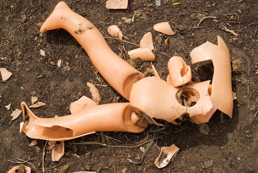 Broken doll on the ground.