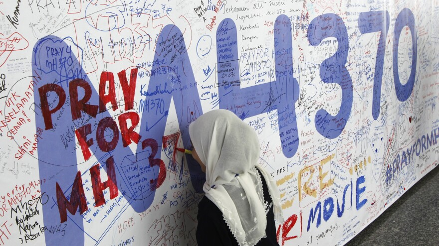 At Kuala Lumpur International Airport on Friday, a woman writes on a banner full of messages about the 239 missing passengers and crew of Malaysia Airlines Flight MH370.