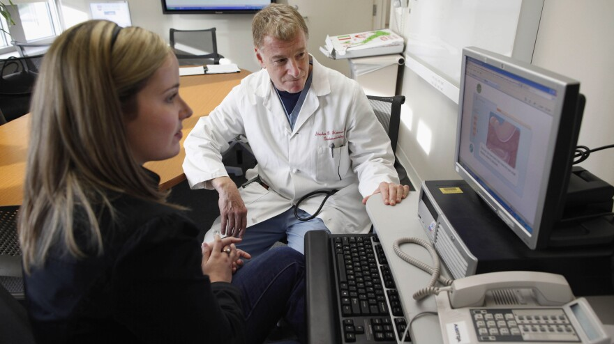 Kristen Miller, a colonoscopy patient, sits with Dr. Stephen Hanauer at the University of Chicago Medical Center in Chicago in 2010. They're looking at an interactive computer program describing benefits and risks of the procedure.