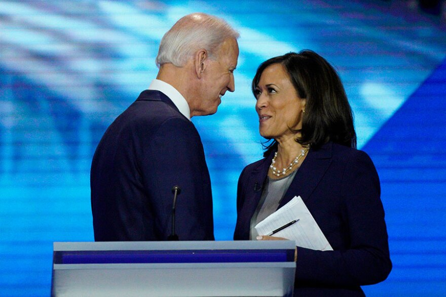 Biden shaking Harris' hand, smiling at each other