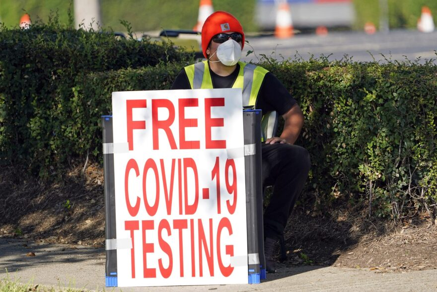 "A photo of a man in a mask holding a sign that says ""free covid-19 testing"""