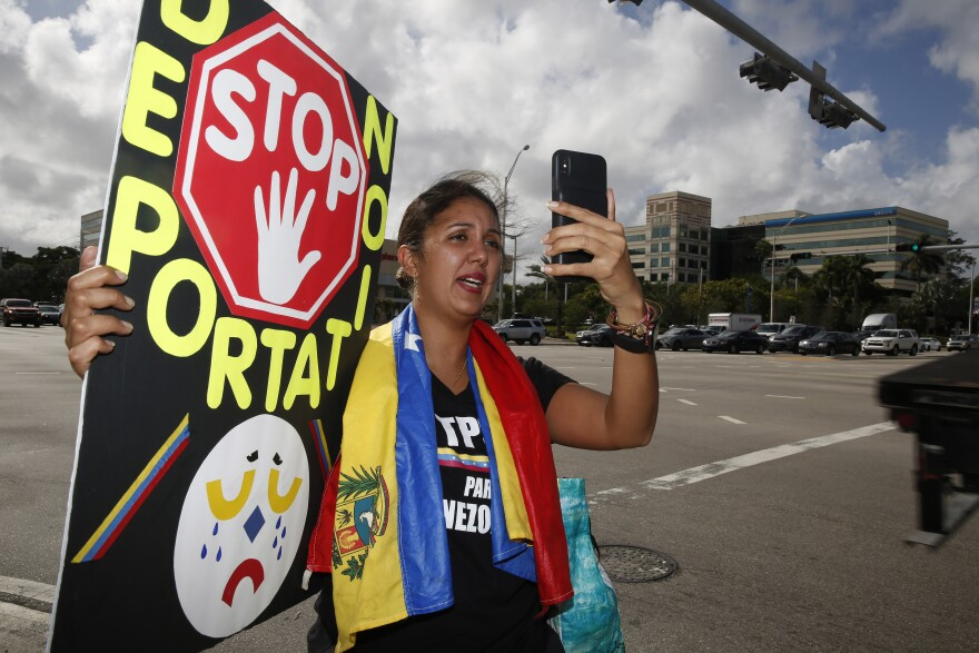 woman holding stop deportation sign