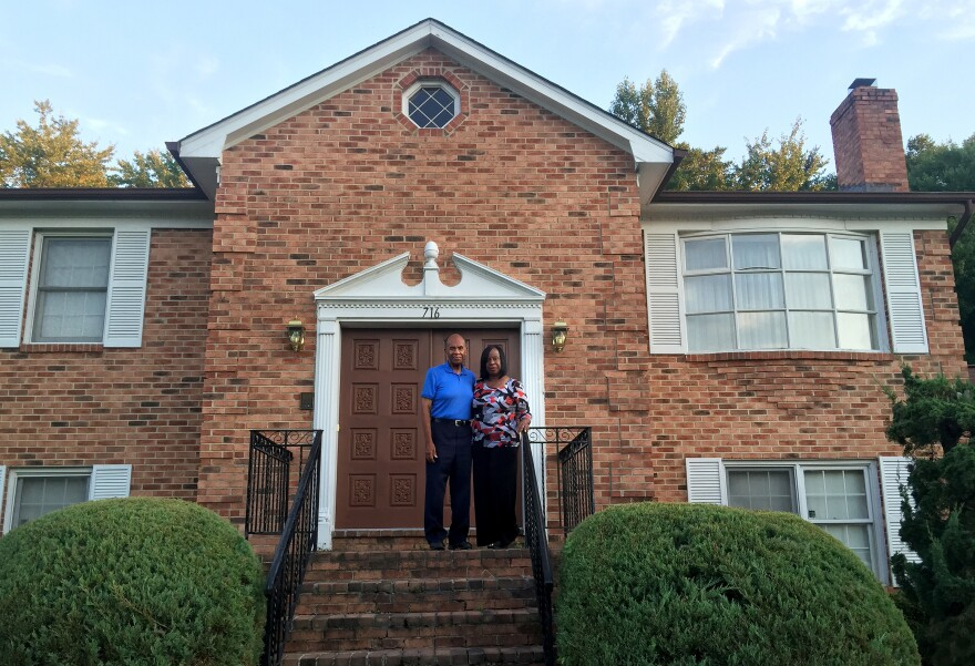 """Grattan (left) and Evelyn Betancourt stand in front of their home in Fort Washington, Md., in one of the wealthiest majority-black counties in the United States: Prince George's, just east of Washington, D.C. But the reality, Grattan says, is """"that many people here, even though they've lived here for many years, are fighting to save their homes"""" — the Betancourts among them."""