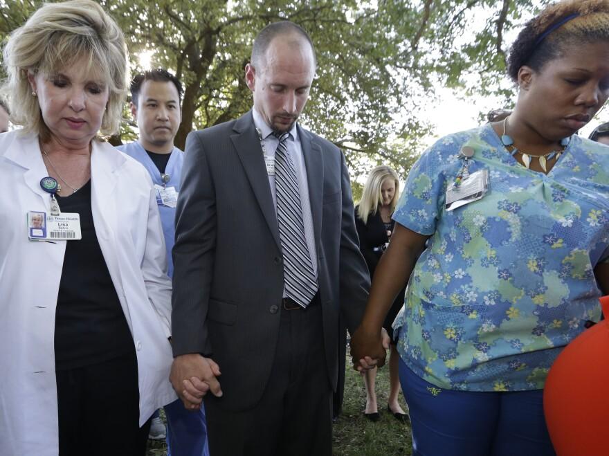 Hospital workers attend a prayer vigil outside Texas Health Presbyterian Hospital on Tuesday.