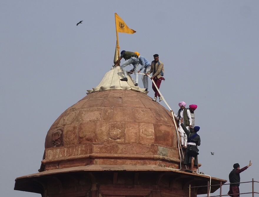 Farmers and their supporters hoist flags over the historic Red Fort monument in New Delhi on Tuesday.