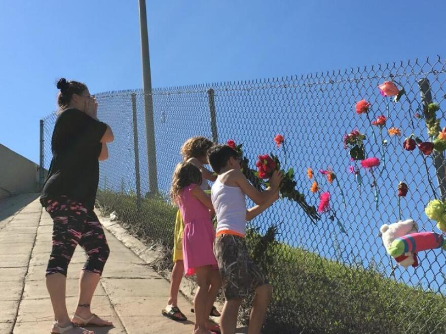 Two children affix a bouquet of flowers to a fence. (News Service of Florida)
