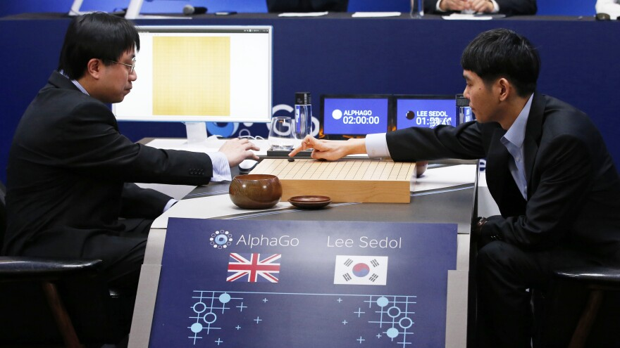 Champion professional Go player Lee Sedol (right) makes a move in his match against Google's artificial intelligence program, AlphaGo, at the Google DeepMind Challenge Match in Seoul, South Korea, Wednesday.