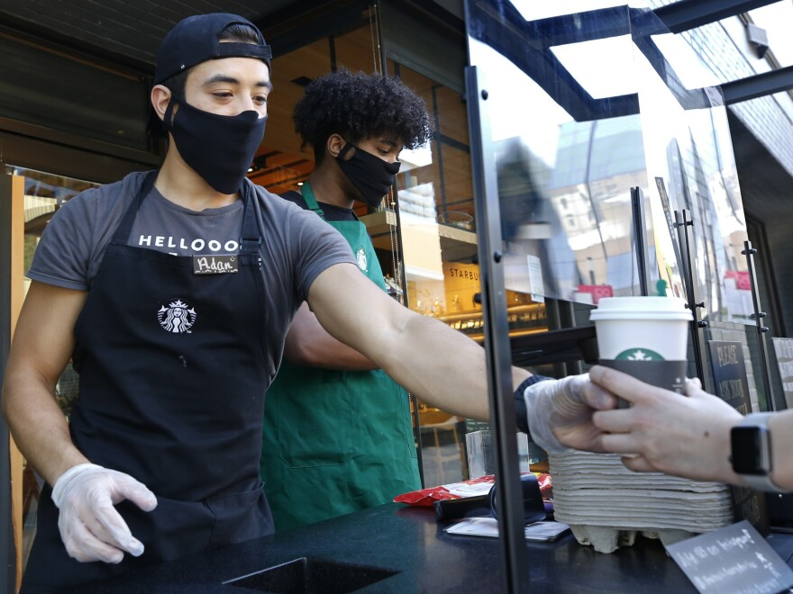 Starbucks shift supervisor Adan Miranda wears a face mask as he serves a drink to a customer while standing behind a plexiglass shield in a booth outside the store in Sacramento, Calif., May 21, 2020.