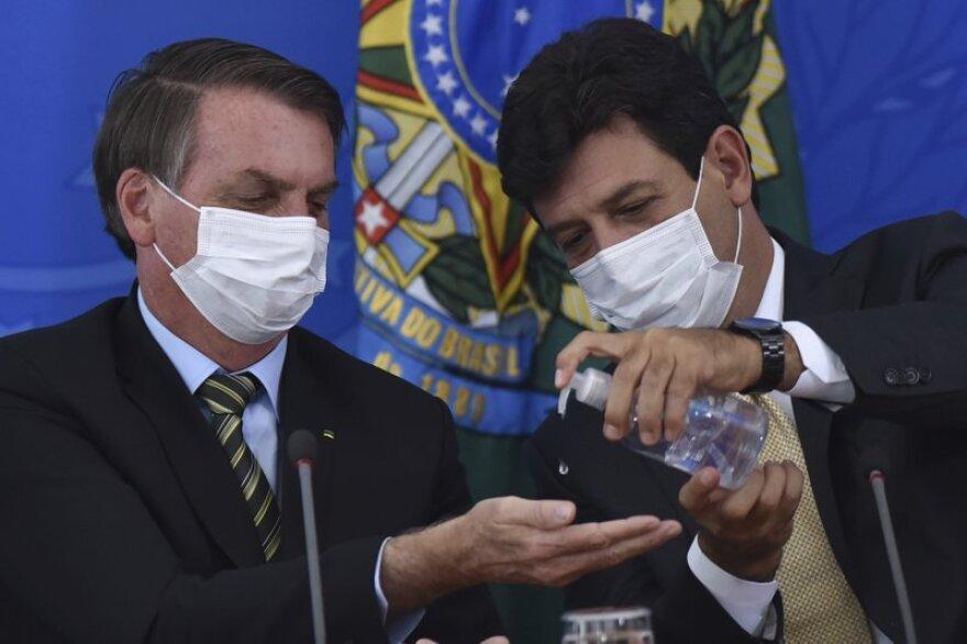 RUDDERLESS SHIP Brazilian Health Minister Luiz Henrique Mandetta (right) gives President Jair Bolsonaro hand sanitizer last month at the Planalto presidential palace in Brasilia