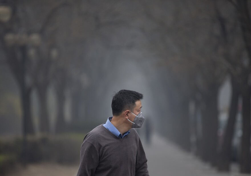 A masked man walks past trees shrouded with pollution haze in Beijing, China.