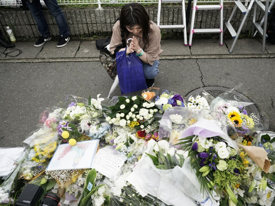 A woman prays to honor the victims of fire at the Kyoto Animation Studio building.