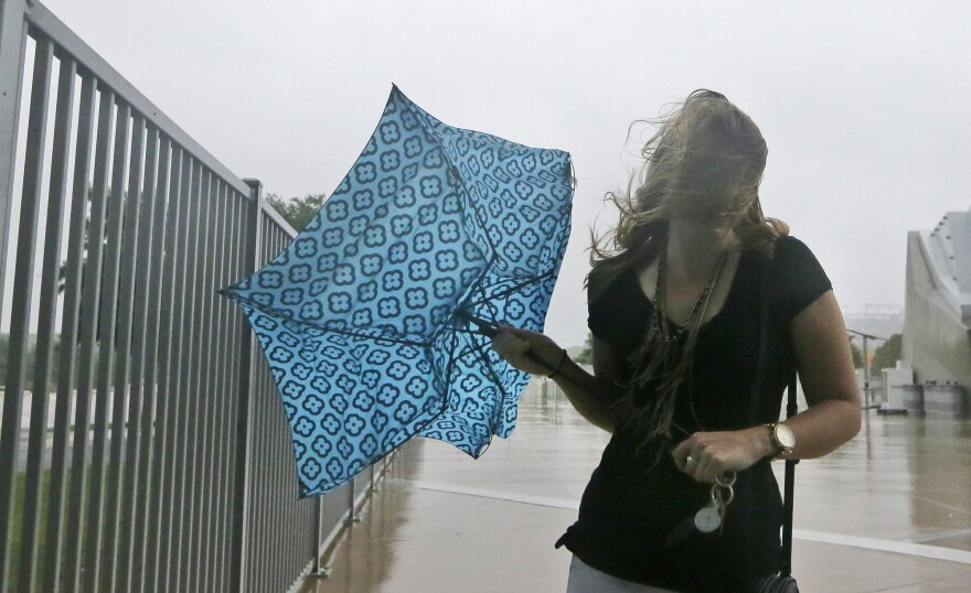 A woman battles with her umbrella during a heavy storm in Arlington in June 2015.