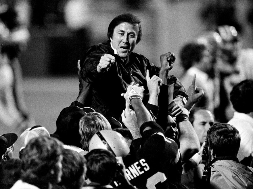 Coach Tom Flores gestures to members of the Los Angeles Raiders as they carry him off the field after their 38-9 victory over the Washington Redskins in Super Bowl XVIII in Tampa Jan. 23, 1984.