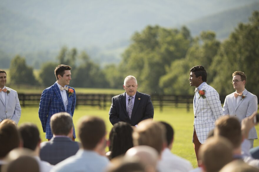 Rep. Denver Riggleman, R-Va., center, officiates the wedding of Alex Pisciarino, left, and Rek LeCounte, right, in July 2019. Some of Riggleman's Republican opponents have seized on Riggleman's decision to officiate a same-sex wedding to argue he is out of step with the GOP.
