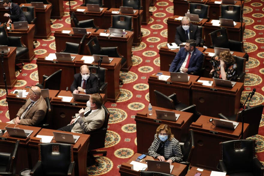 Lawmakers, many wearing masks, sit at their desks inside the House chamber Monday, April 27, 2020, in Jefferson City, Mo.