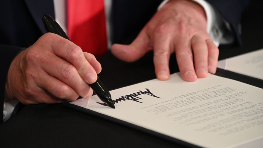 President Trump signs executive actions regarding coronavirus economic relief during a news conference in Bedminster, N.J., on Saturday. A number of lawmakers are criticizing the measures' substance and constitutionality.