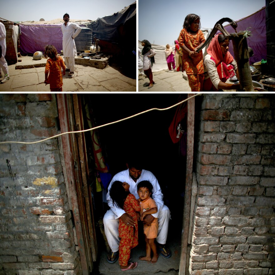 Akhtar Ali, 44, with two of his 10 children, lives with his family along the floodplain of the Yamuna River. Land is available there — Ali bought his — but the settlement he lives in is not authorized by the government. When the river floods, he's forced to move the family to higher ground.