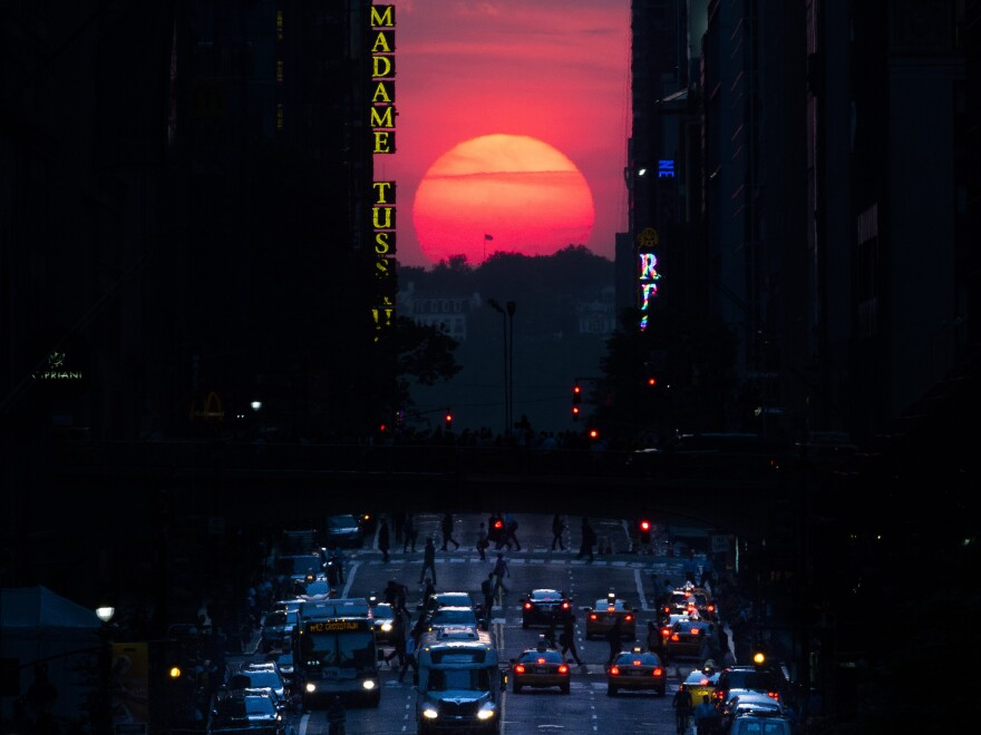 """The sun sets along 42nd Street in Manhattan in 2013 during a semi-annual phenomenon known as """"Manhattanhenge,"""" when the sun aligns perfectly with the city's transit grid."""