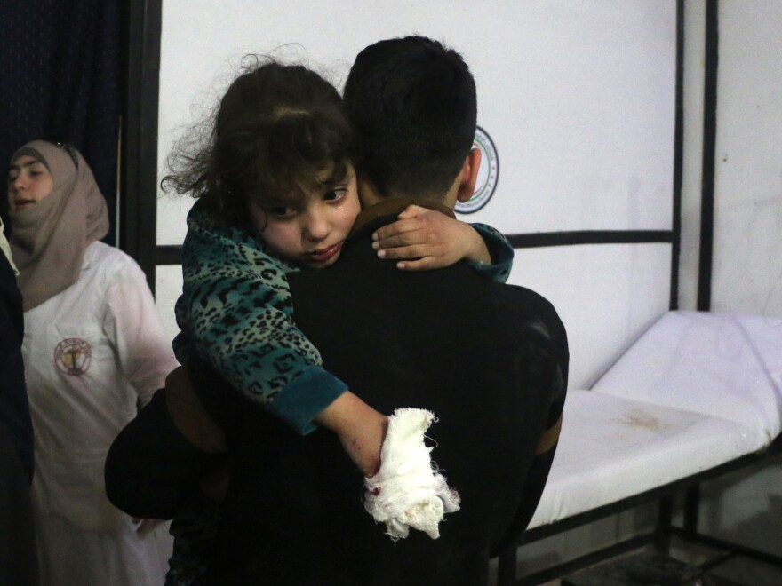 A lightly wounded Syrian girl is carried by a man at a makeshift clinic following Syrian government bombardments in Douma, in the besieged Eastern Ghouta region on the outskirts of the capital Damascus on Thursday.