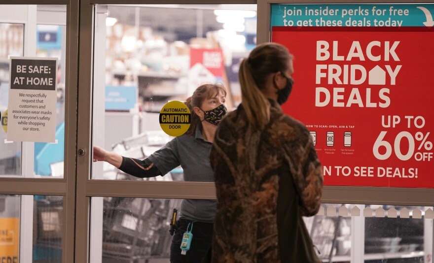 Woman standing in from of store's sliding glass doors with large Black Friday sale sign on it as woman employee unlocks the dor.