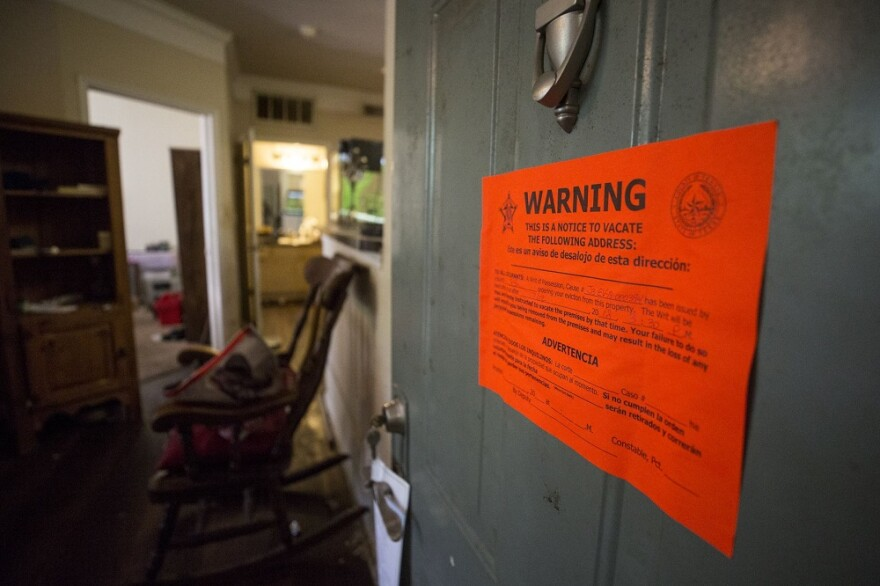 Photo of eviction notice taped to open door.
