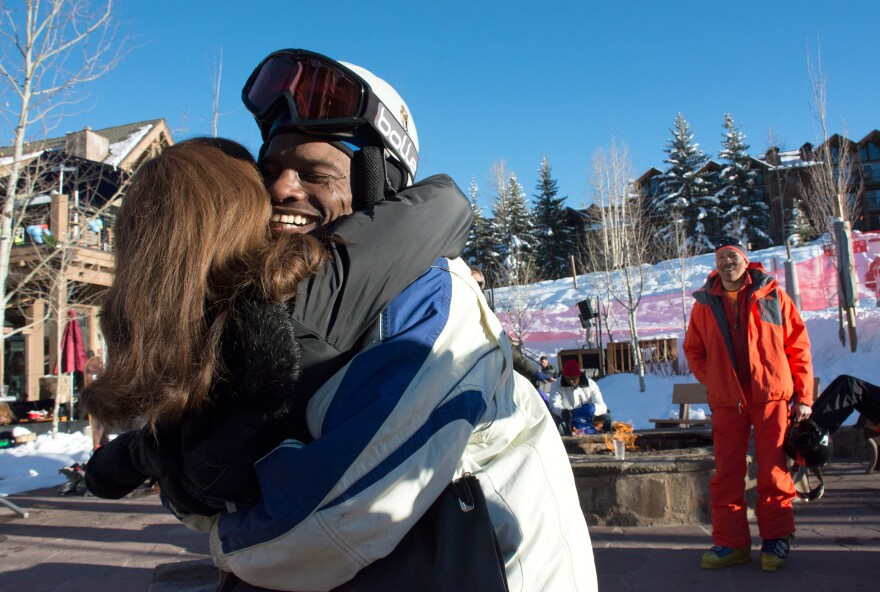 Todd Hood of Long Beach, Calif., reunites with his friend Laura James at Black Ski Summit. He and Jerry Elie (right) of Akron, Ohio, were relaxing by the fire pit after skiing when they spotted Laura.
