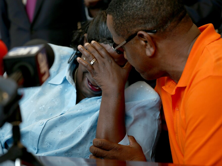 Lavall Hall's mother, Catherine Daniels, is comforted by her cousin Alfonzo Hill as she speaks with the media in February. Hall, who was schizophrenic, was fatally shot by police officers earlier this year.