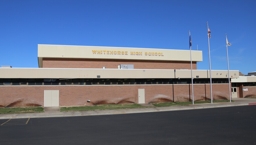 """A large brick building with the words """"whitehorse high school"""" on it and flags flying."""