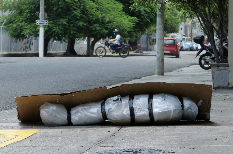 An abandoned corpse lies on the sidewalk in Guayaquil, Ecuador, on April 6. Due to bottlenecks in collecting the dead, people were wrapping the bodies of deceased relatives in plastic and bed sheets and, in some cases, moving them outside because of the odor.