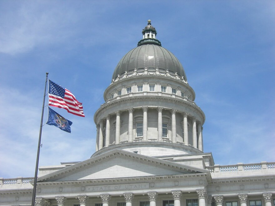 A photo of the Utah State Capitol with the American flag and Utah State flag in front of it.