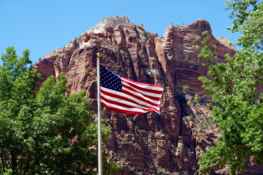 Photo of an American flag waving in front of a red rock cliff