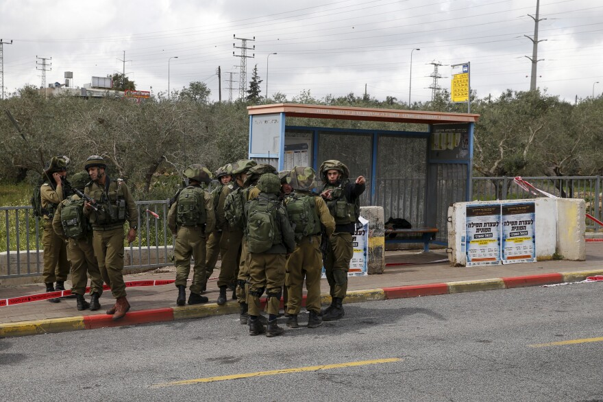 Israeli soldiers gather near where the Israeli military said two Palestinians stabbed and wounded an Israeli woman outside the Jewish settlement of Ariel in the West Bank in March 2016. The Palestinian attackers were shot and killed in response.