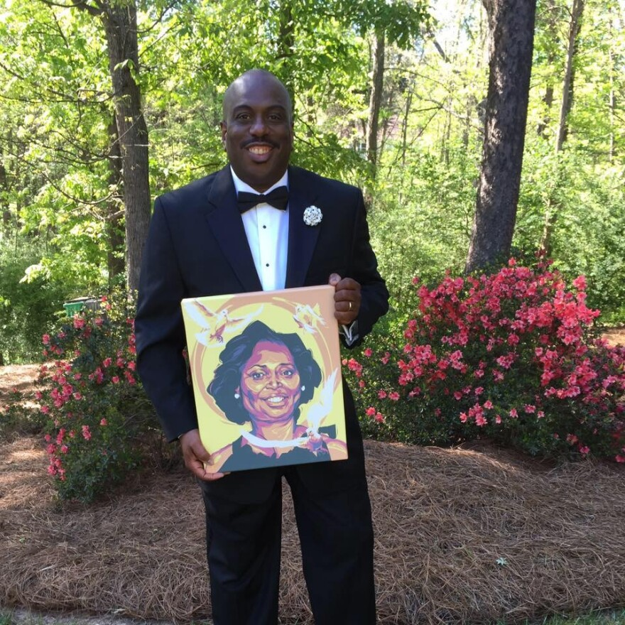 Malcolm Graham holds a portrait of his sister, Cynthia Hurd.