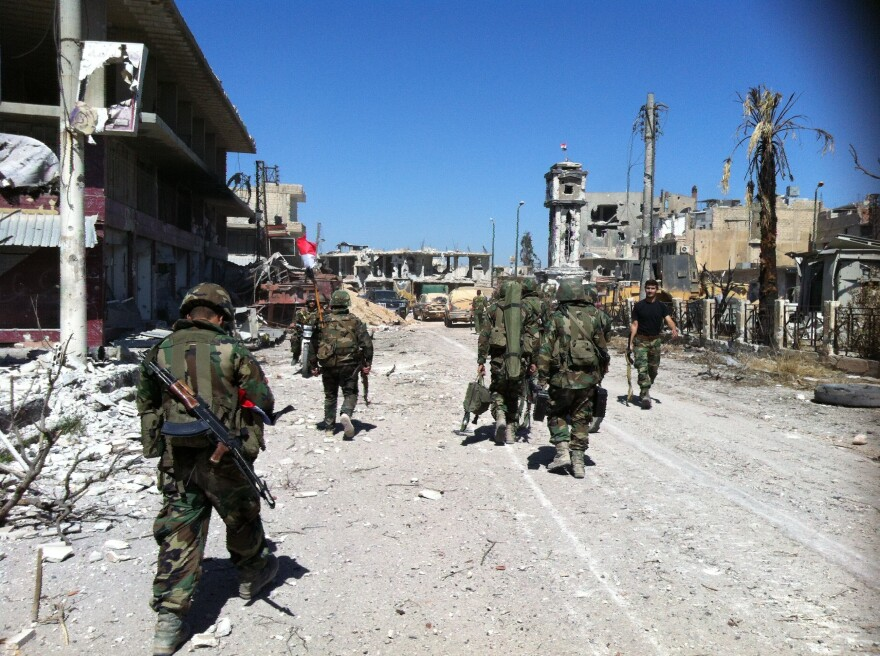 Syrian army's soldiers walk in a street left in ruins on Wednesday in the city of Qusair in Syria's central Homs province.
