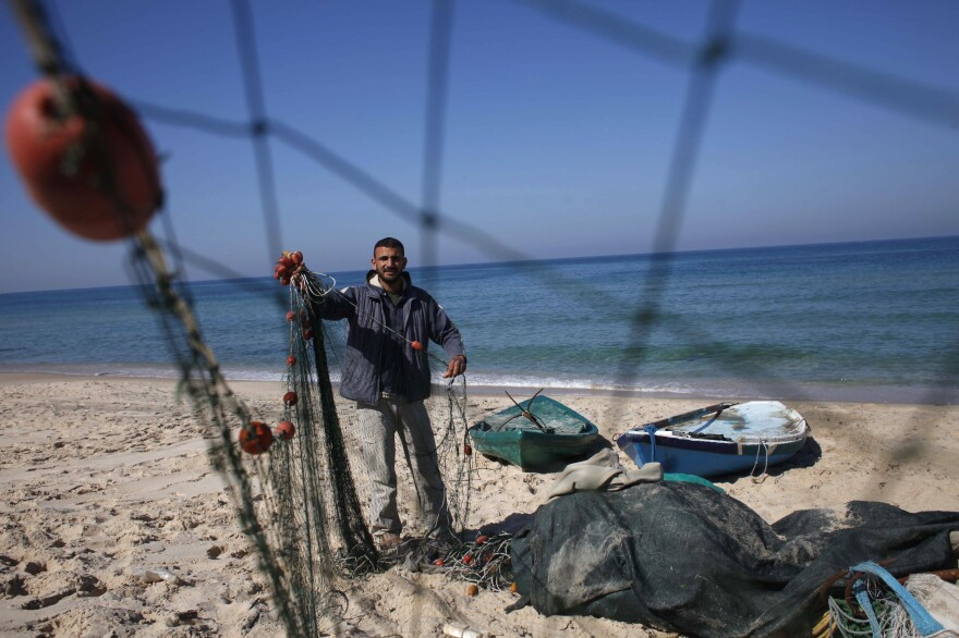 Palestinian fisherman Judah Abughorab, who said he pulled the bronze Apollo statue from the seabed last August, prepares his fishing net on the beach of Deir El-Balah in the central Gaza Strip on Feb. 9.