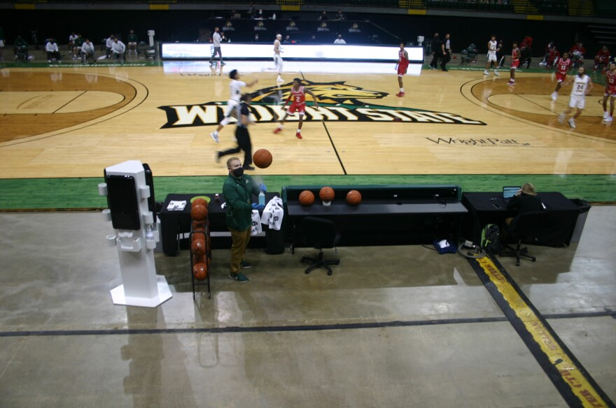 A Wright State staff-member disinfects game balls with a spray bottle and towel.