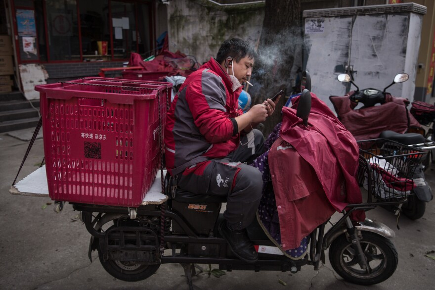 A worker with an empty cart on his scooter checks his phone.