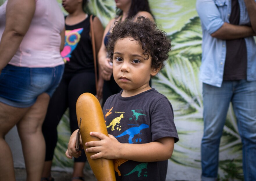 Tito Matos' son Marcelo Matos Reyes, 3, holds a guiro, a percussive instrument, as part of the Plena.