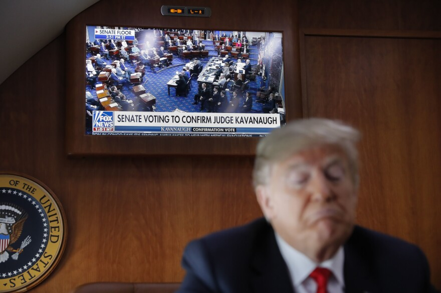 A live television broadcast of the Senate confirmation vote of Supreme Court nominee Brett Kavanaugh is displayed with President Donald Trump, on board Air Force One, Saturday, Oct. 6, 2018. Trump was traveling from Washington enroute to Topeka, Kan., for a campaign rally. (AP Photo/Pablo Martinez Monsivais)