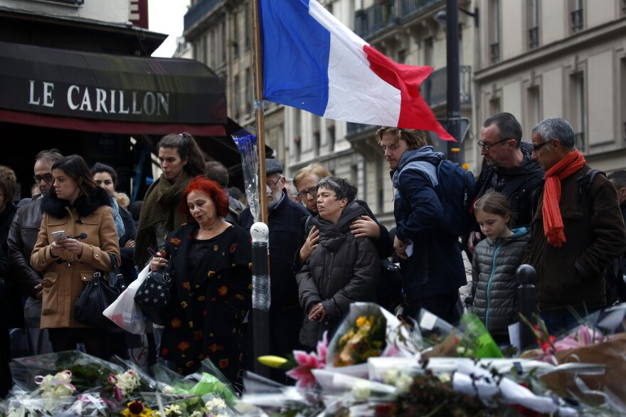 People gather outside Le Carillon, a bistro in Paris' 10th arrondissement that was attacked on Friday.
