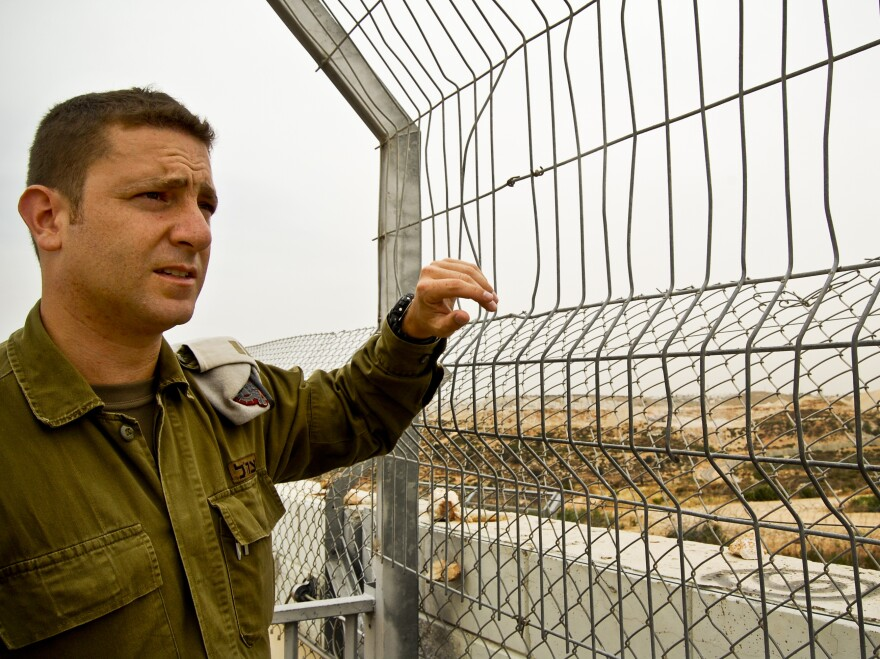 """Israeli army Capt. Barak Raz stands on a concrete wall that is part of the barrier separating Israelis and Palestinians in the West Bank. Soldiers climb to this spot during Palestinian protests to disperse crowds with tear gas or a foul-smelling liquid nicknamed """"skunk."""""""