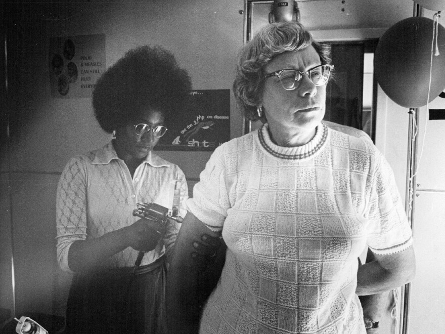 Jackie Carnegie immunizes Mabel Haywood in a Colorado Health Department immunization van in 1972. Shots for measles and other infectious diseases were offered.